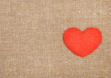 Klädd med filt röd hjärta på säckväven Royaltyfri Fotografi