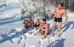 Klädde av män och en kvinna lägger på snövit fluffig snö, på Royaltyfri Fotografi