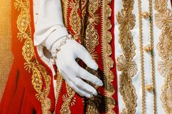 Kläder av en historisk imperialistisk kvinna med röda beståndsdelar, en hand i vita handskar Arkivfoton