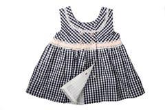 Kläder för barn En svartvit rutig klänning med stiftet royaltyfria bilder