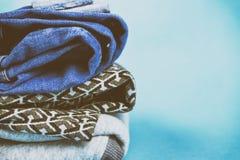 Kläder för grov bomullstvill för ` s för varma och trendiga kvinnor vek på en kulör bakgrund Arkivbild