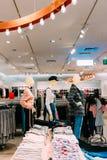 Kläder för iklädd kvinnlig kvinna för skyltdockor tillfällig och kläder på hyllor och hängare arkivbild