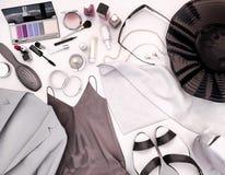 Kläder för kvinna` s, hudomsorg och skönhetsmedel lokaliseras på en vit Arkivbild