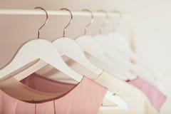 Kläder för kvinna` s i rosa färger tonar på en vit hängare Royaltyfri Fotografi