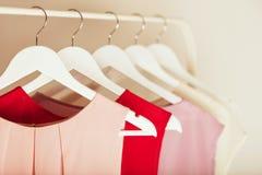 Kläder för kvinna` s i rosa färger tonar på en vit hängare Arkivfoto