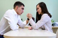 Kläder för man som och för kvinna i regeringsställning kämpar på hans händer över skrivbordet i kontoret arkivbilder