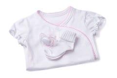 Kläder för newborns på en vit bakgrund Arkivbilder