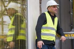 Kläder för säkerhet för byggnadsarbetare som bärande skyddande lägger mot materialet till byggnadsställning Arkivfoto