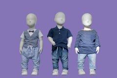 Kläder för tre ungar för skyltdockor iklädda trendiga royaltyfria bilder