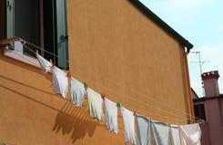 kläder hängde ut för att torka utanför ett orange hus arkivfoto