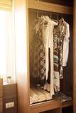 Kläder hänger på en hylla i ett lager för märkes- kläder, modern garderob med rad av kläder som hänger i garderob, tappningrum Royaltyfri Bild