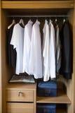 Kläder hänger på en hylla i ett lager för märkes- kläder, modern garderob med rad av torkdukar som hänger i garderob, tappningrum Arkivbilder
