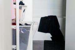 Kläder i hemliga enhetskorgorganisatörer, med badrummet i bakgrunden och den svarta handduken som hänger över bad, badar fotografering för bildbyråer