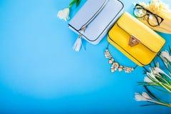 Kläder och tillbehör för vår kvinnlig med blommor Stilfulla handväskor med basker, halsduken och smycken Mode royaltyfria bilder