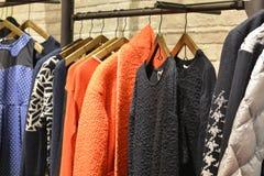 Kläder på kuggar i mode shoppar arkivbilder