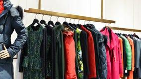 Kläder på kuggar i mode shoppar arkivbild