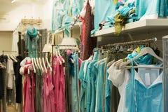 Kläder shoppar med blåa klänningar Royaltyfri Foto