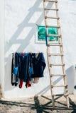 Kläder som hänger för att torka framme av hus arkivbilder