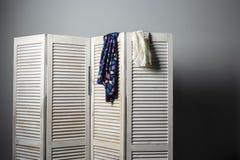Kläder som hänger på den vita vikningskärmen royaltyfri bild