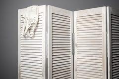 Kläder som hänger på den vita vikningskärmen arkivbilder