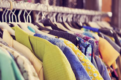 Kläder som hänger på en kugge i en loppmarknad Royaltyfria Bilder