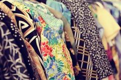 Kläder som hänger på en kugge i en loppmarknad arkivbild
