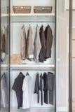 Kläder som hänger på stången i den vita garderoben fotografering för bildbyråer