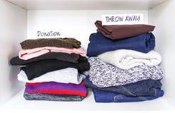 Kläder som sorterar i garderob på vit hyllabakgrund Donation kastar bort pappers- anmärkningar fotografering för bildbyråer