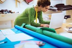 Kläderformgivare som arbetar i hennes atelier royaltyfri foto