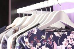 Klädersamling på hängare i modeboutiquelager Arkivbild