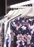 Klädersamling på hängare i modelager Arkivfoto
