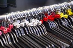 Klädhängare på kromstången med formatetiketter Arkivfoton