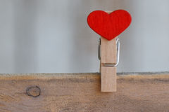 Klädnypa i formen av en hjärta på träbakgrund arkivbilder
