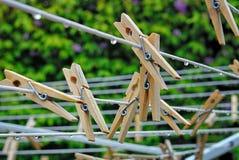 Klädnypor på en utomhus- tvätteri fodrar som nedgångar för ett ljust regn arkivfoton