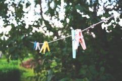 Klädnypor på ett rep i byn arkivbild