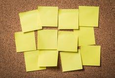 Klämde fast pappers- anmärkningar på korkbräde arkivbild