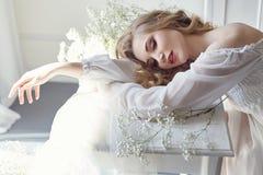 Klänning för vitt ljus för flicka och lockigt hår, stående av kvinnan med blommor som är hemmastadda nära fönstret, renhet och ha fotografering för bildbyråer