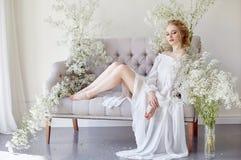 Klänning för vitt ljus för flicka och lockigt hår, stående av kvinnan med blommor som är hemmastadda nära fönstret, renhet och ha arkivbild