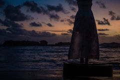 Klänningkontur på solnedgången, härlig ocan bakgrund fotografering för bildbyråer