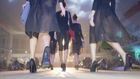 Klänningshowen, gruppcatwalkmodeller på hög-heeled i svart identisk genomskinlig kappa går ner landningsbana på presentationen av lager videofilmer