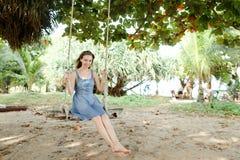 Klär bärande jeans för ung lycklig kvinna och rida på gunga, sand i bakgrund royaltyfri fotografi