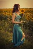 Klär den caucasian kvinnan för brunetten i blått på parkera i blommor på hållande solrosor för en sommarsolnedgång arkivfoton