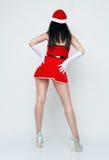 Klär den härliga och sexiga kvinnan för den tillbaka platsen som sexiga Santa Claus Royaltyfri Fotografi