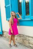 Klär det utomhus- fotoet för mode av den härliga unga kvinnan med blont hår som bär eleganta rosa färger, att posera utomhus Royaltyfri Bild