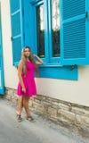 Klär det utomhus- fotoet för mode av den härliga unga kvinnan med blont hår som bär eleganta rosa färger, att posera utomhus Arkivbild