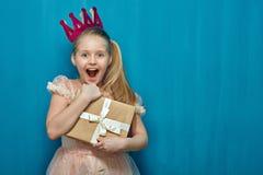 Klär krönar bärande rosa färger för lycklig överraskande flicka och den hållande gåvan arkivfoto