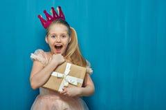 Klär krönar bärande rosa färger för lycklig överraskande flicka och den hållande gåvan royaltyfri fotografi