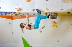 Klättra för ung kvinna som är uppochnervänt i bouldering idrottshall Royaltyfria Bilder