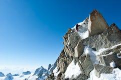 Klättra i Chamonix Klättrare på den snöig kanten av Aiguille du Royaltyfria Foton