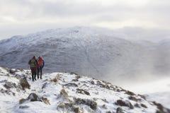 Klättra till och med snön och isen arkivfoto